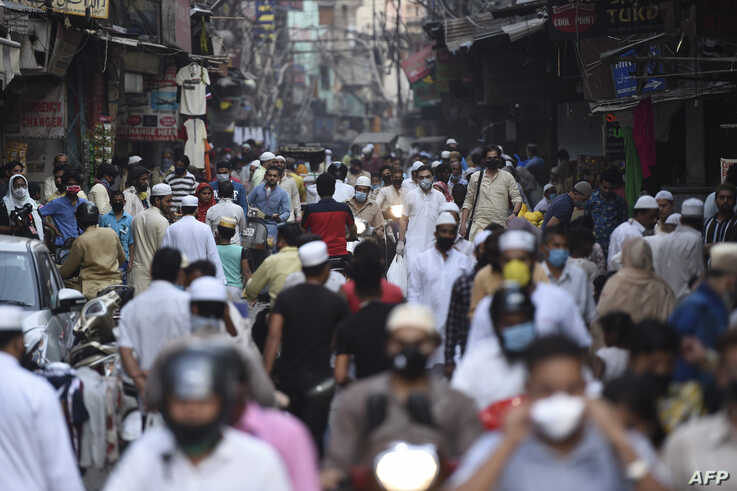 People gather at a market on the last Friday of Ramadan after the government eased restrictions imposed as a preventive measure…