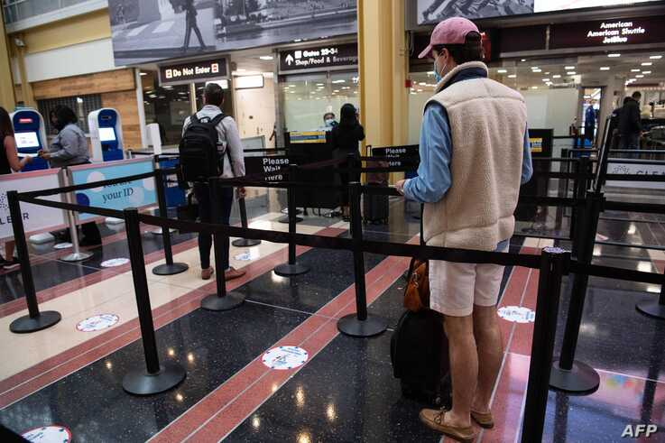 Two people wait in line at a security checkpoint at a virtually deserted Reagan National Airport in Arlington, Virginia, on May…