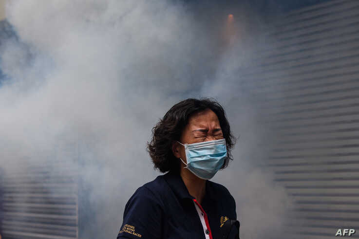 A woman reacts after riot police fired tear gas to disperse protesters taking part in a pro-democracy rally against a proposed…