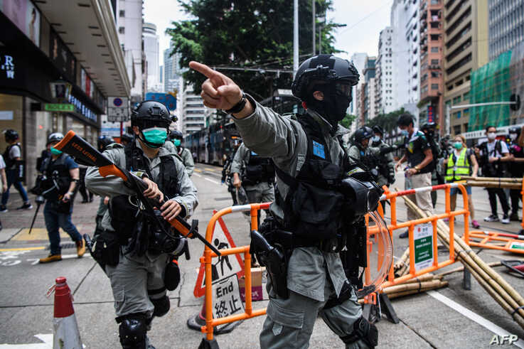 Riot police clear up debris left by protesters attending a pro-democracy rally against a proposed new security law in Hong Kong…