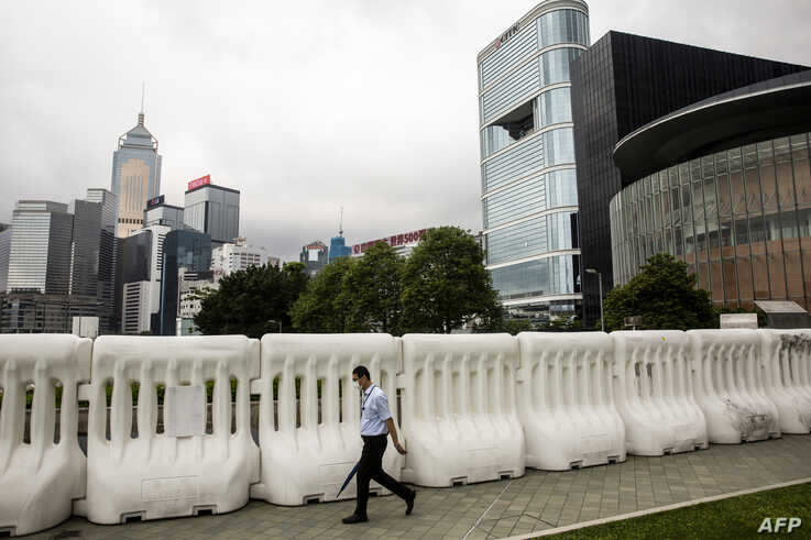 A man walks past extra barricades that have been erected near the Legislative Council in Hong Kong on May 26, 2020, ahead of…