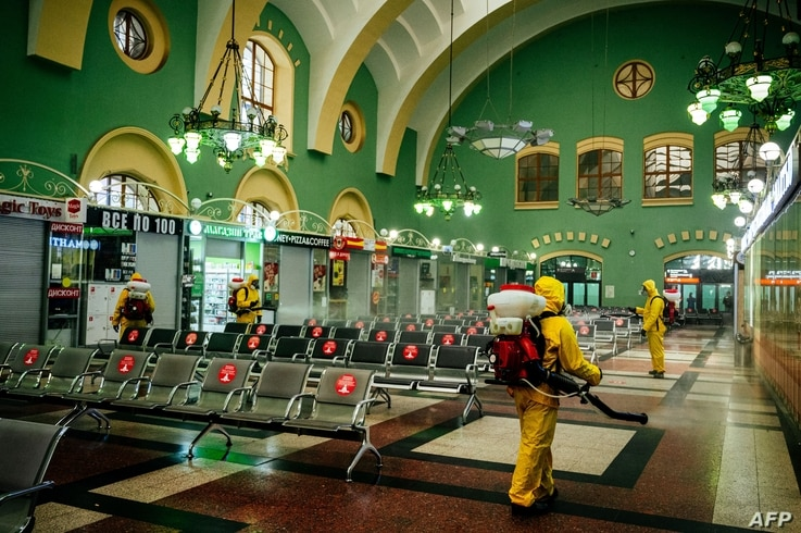 Servicemen of Russia's Emergencies Ministry wearing protective gears disinfect Moscow's Kazansky railway station on May 28,…