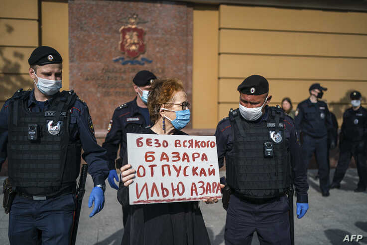 Police officers detain Russian photographer Victoria Ivleva (C) during a solo picket in support of journalist and activist Ilya…