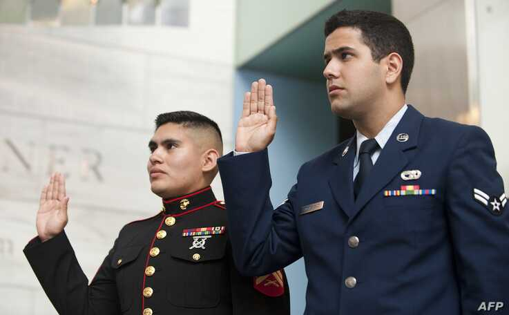 US Marine Corporal Pablo Olvera (L), originally of Mexico, and Air Force Airman First Class Ricardo Sanchez Cano (R) take the…