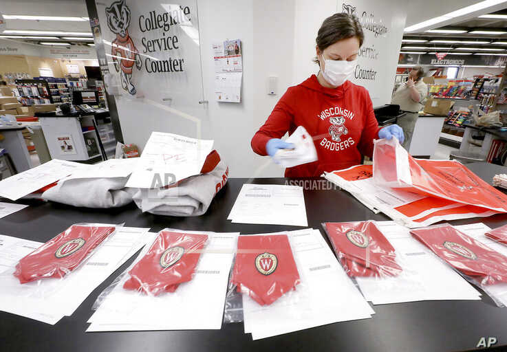 In this Tuesday, May 5, 2020 photo, University of Wisconsin Bookstore worker Stephanie Blaser packages GPA honor stoles…