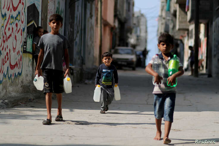 Palestinian boys carry bottles of water as they walk in Al-Shati refugee camp in Gaza City October 23, 2019. Picture taken…