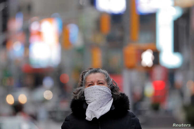 A woman walks in Times Square as a polar vortex brought cold temperatures to the region  in the Manhattan borough of New York…