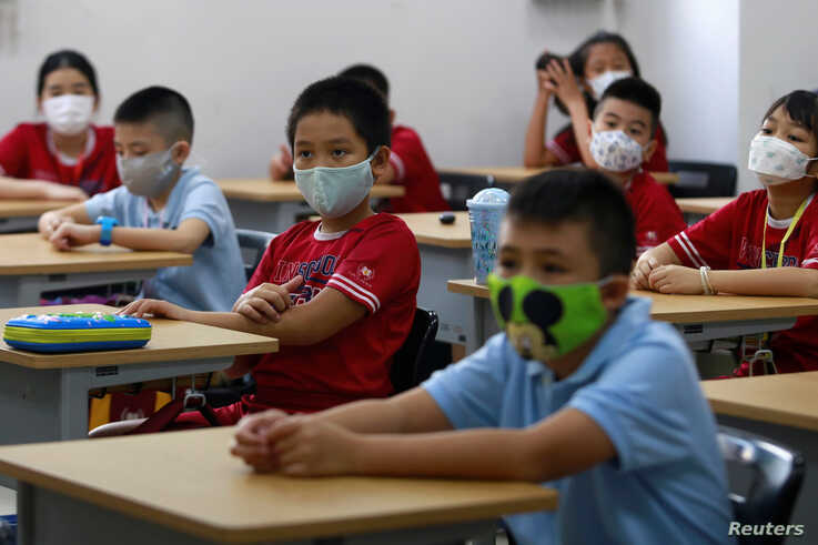 Primary school students wearing masks attend their first day of class after the government eased a nationwide…