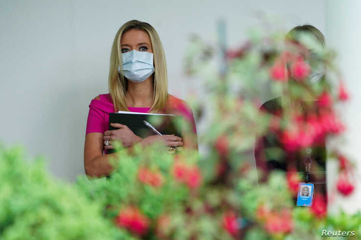 White House Press Secretary Kayleigh McEnany wears a protective face mask as she stands behind roses listening as U.S…