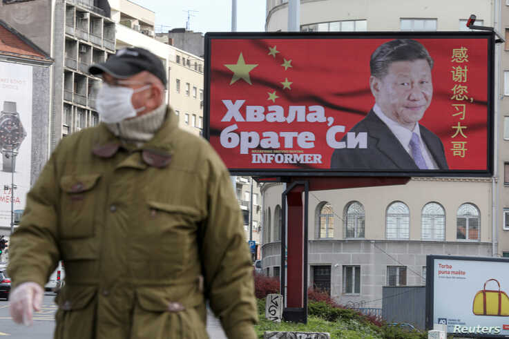 FILE PHOTO: A man wearing a protective mask passes by a billboard depicting Chinese President Xi Jinping as the spread of the…