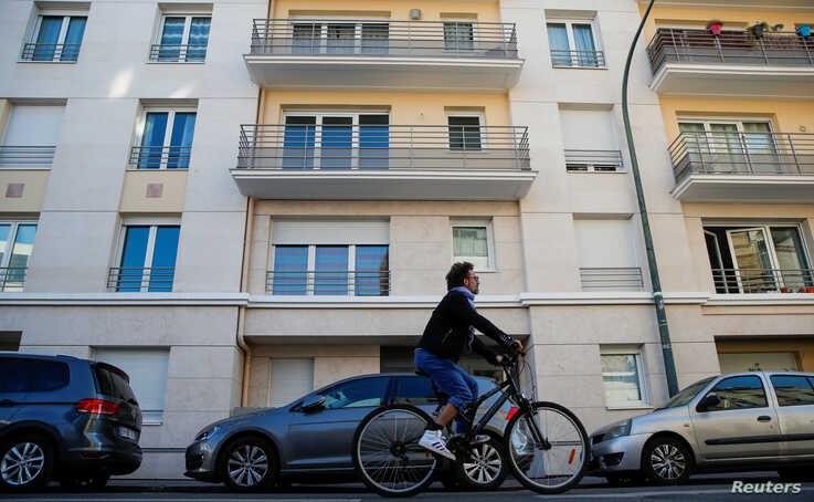 FILE PHOTO: A man rides a bicycle past an apartment building where Rwanda genocide suspect Felicien Kabuga was arrested in…
