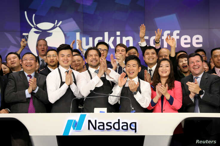 FILE PHOTO: Jenny Qian Zhiya CEO of Luckin Coffee, and Charles Zhengyao Lu, non-executive chairman of Luckin Coffee, ring the...