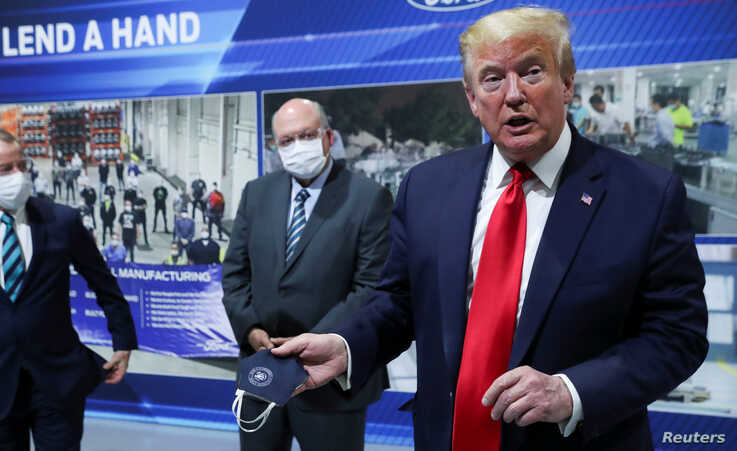 U.S. President Donald Trump holds a protective face mask with a presidential seal on it that he said he had been wearing…