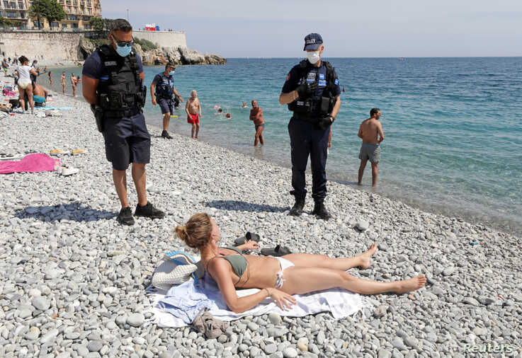 Municipal police officers wearing face masks talk to a woman, at the Promenade des Anglais, in Nice.