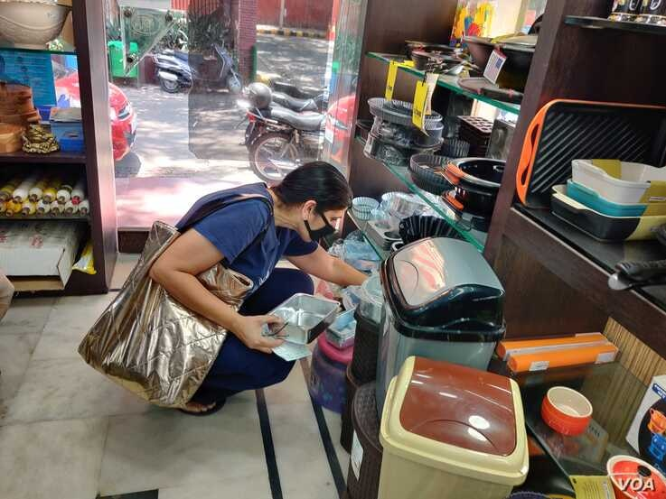 A customer turns up to buy baking tins -- in Delhi, like much of the world, cooking and baking has been a therapy for people confined indoors. (Anjana Pasricha/VOA)