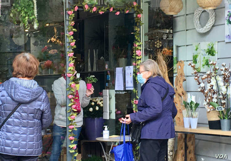 A Paris flower store, flouting French lockdown rules, sells lily of the valley flowers for May Day. (Lisa Bryant/VOA)