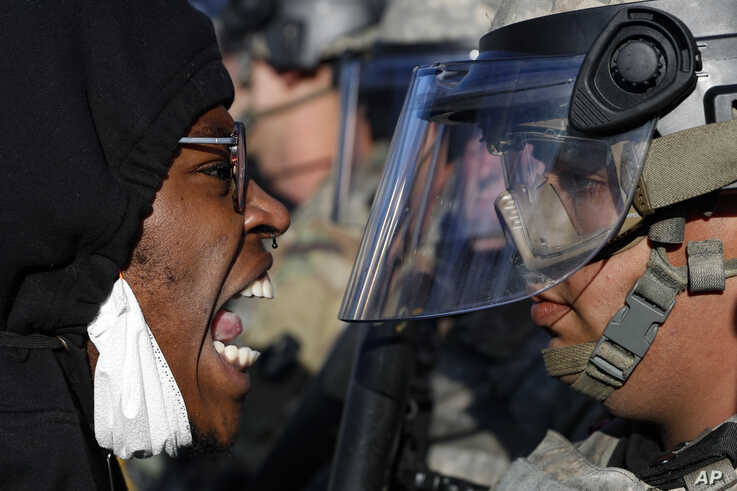 Protesters and National Guardsmen face off on East Lake Street, Friday, May 29, 2020, in St. Paul, Minn.  The massive protests…