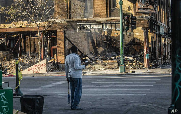 A man looks at the destruction aftermath of businesses along Lake Street, May 31, 2020, in Minneapolis.