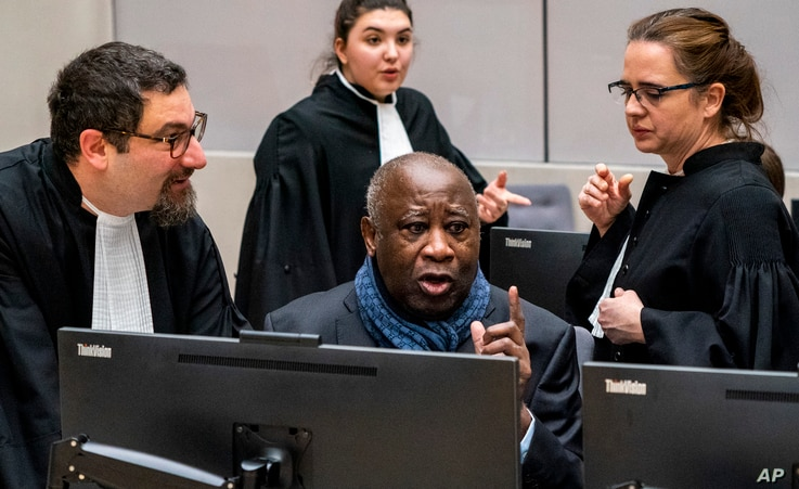 Former Ivory Coast president Laurent Gbagbo talks to his members of his legal team at the International Criminal Court in The Hague, Netherlands, Feb. 6, 2020.