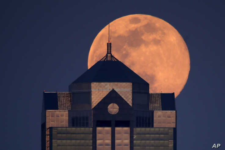 The supermoon rises behind a downtown office building in Kansas City, Mo., Tuesday, April 7, 2020. (AP Photo/Charlie Riedel)