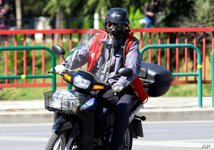 A man wearing a tear gas mask drives his motorcycle during a lockdown order by the Albanian government to prevent the spread of…