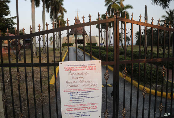 A sign hanging on a locked gate in front of the Ermita de la Caridad church in Miami indicates that the church is closed