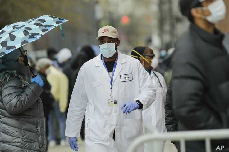 A medical worker walks past people lined up at Gotham Health East New York, a COVID-19 testing center