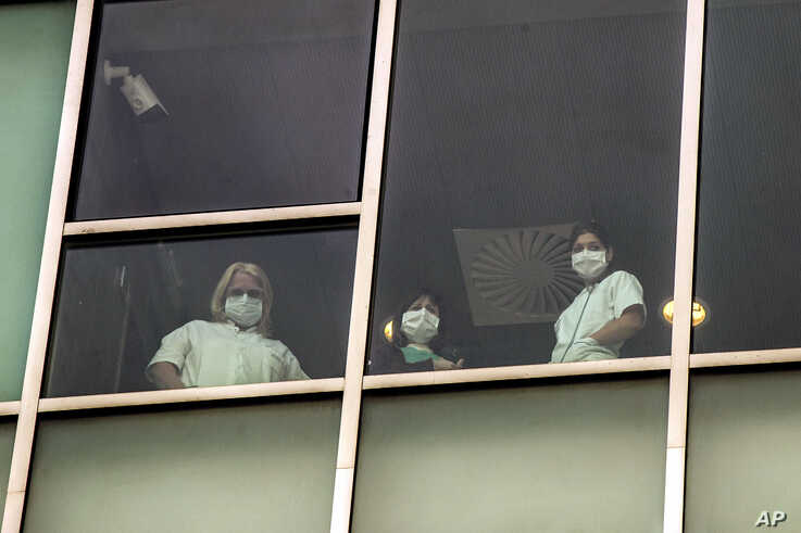 Nurses look out from a window of the San Luca Hospital in Milan, Italy, April 30, 2020. Italy is in its eighth week…