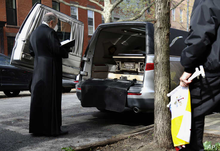 Monsignor Kieran Harrington, Vicar for Communications for the Diocese of Brooklyn, prays over the body of the Rev. Jorge Ortiz-Garay in the Brooklyn borough of New York as they prepare to transport his body to JFK International Airport, May 3, 2020.
