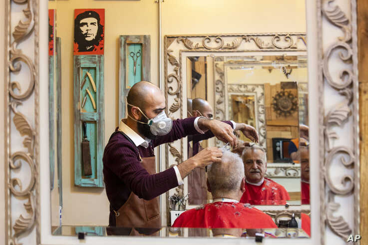 A barber wears a mask to help prevent the spread of the coronavirus as he cuts a customer's hair at his salon, in Beirut,…