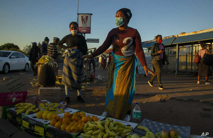 Street vendors, wearing face masks as a precaution against the spread of the new coronavirus, sell fruit on the street corner…