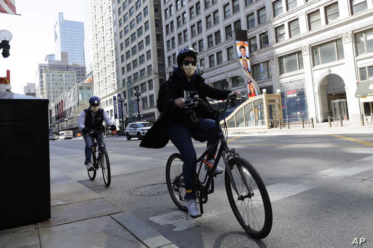 People wear mask as they ride bicycles in downtown Chicago, May 7, 2020.