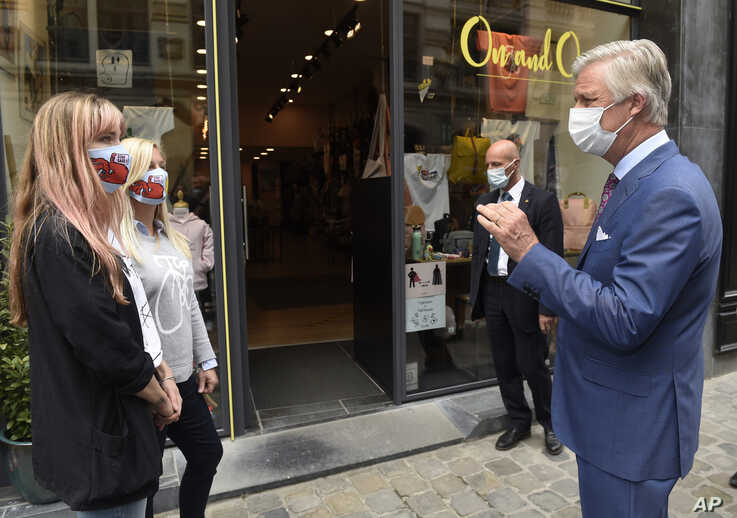Belgium's King Philippe, right, wearing a mouth mask, speaks with shopkeepers in Brussels, Sunday, May 10, 2020.