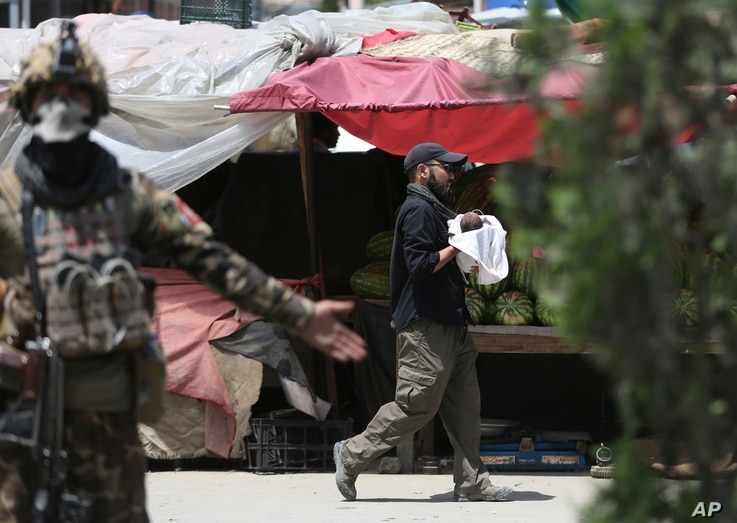 An Afghan security officer carries a baby after gunmen attacked a maternity hospital, in Kabul, Afghanistan, Tuesday, May 12,…