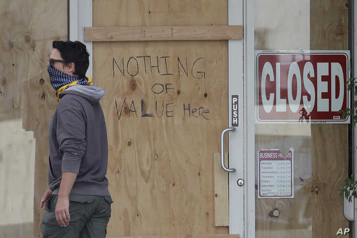 A man wears a face mask while walking past a hand written sign advising that nothing of value is inside a boarded up Union…