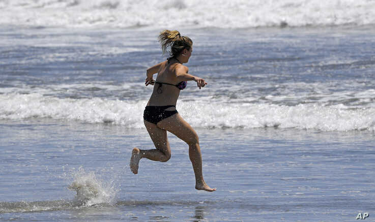 A swimmer runs into the ocean at Venice Beach during the coronavirus outbreak, Wednesday, May 13, 2020, in Los Angeles. Los…