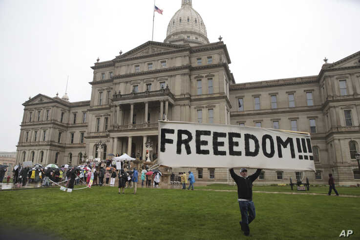 A protester carries a sign during a rally against Michigan's coronavirus stay-at-home order at the State Capitol in Lansing,…