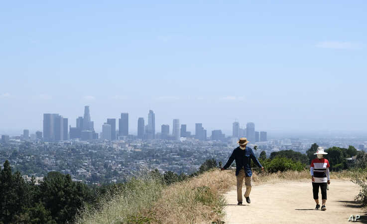 Walkers use recently re-opened hiking paths inside Griffith Park, Thursday, May 14, 2020, in Los Angeles. (AP Photo/Chris…