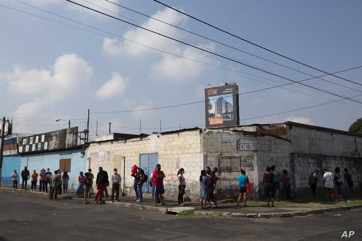 "People stand in line to buy food on a small grocery store in the ""La Reformita"" neighborhood during a lockdown in Guatemala…"