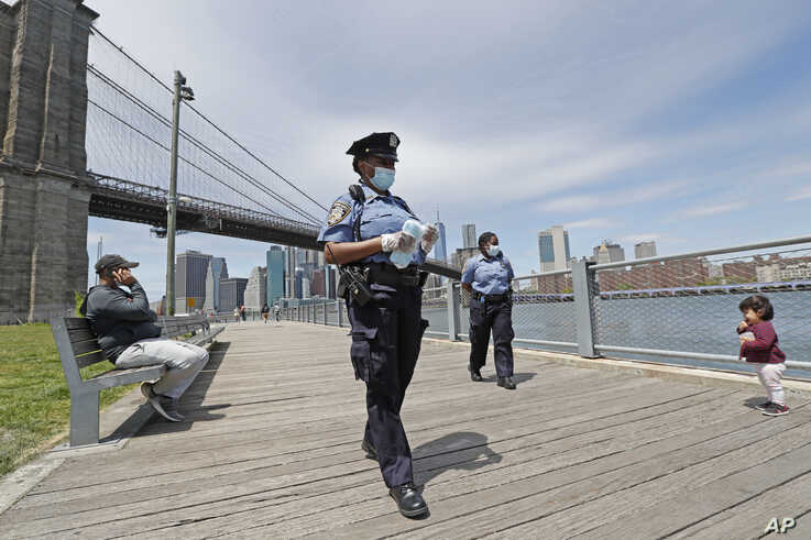 A youngster approaches a team of New York City police officers as they walk with face masks to hand out to anyone who needs or asks for one during the current coronavirus outbreak, Sunday, May 17, 2020, in Brooklyn Bridge Park in New York.
