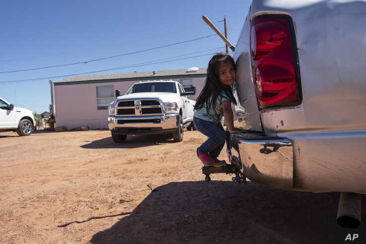 FILE - A little girl plays in her family compound in Tuba City, Ariz., April 22, 2020.