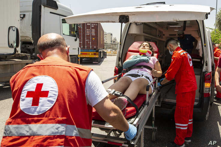 Lebanese Red Cross volunteers help an injured anti-government protester during scuffles between protesters and riot police at…