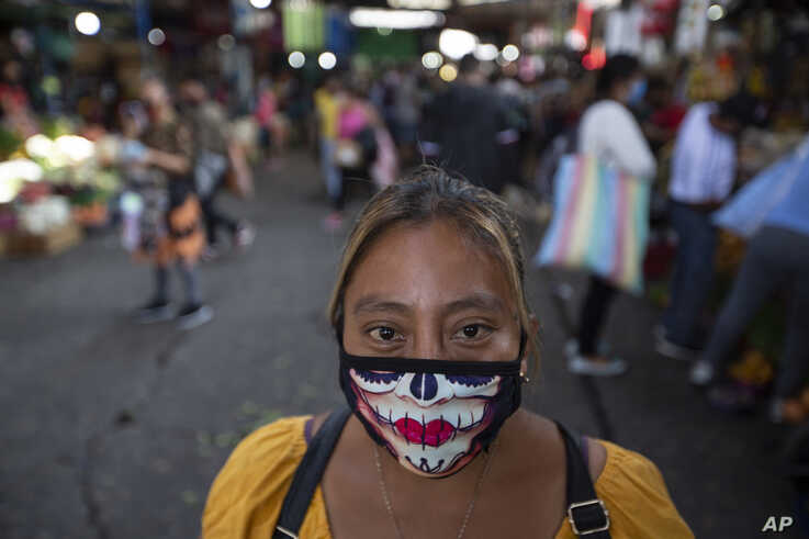 A woman wearing a mask against the spread of the new coronavirus poses for a photo at La Terminal market in Guatemala City,…
