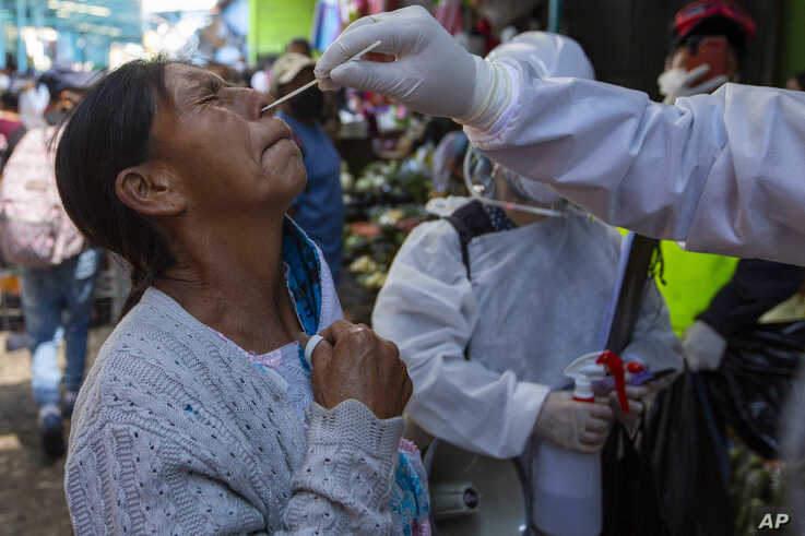A health worker takes a sample from a vendor to test for COVID-19 at La Terminal market in Guatemala City, Thursday, May 21,…