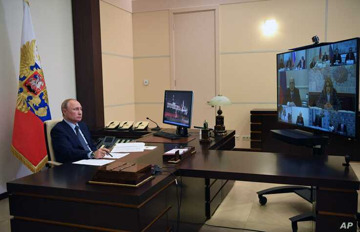 Russian President Vladimir Putin attends a cabinet meeting via teleconference at the Novo-Ogaryovo residence outside Moscow…