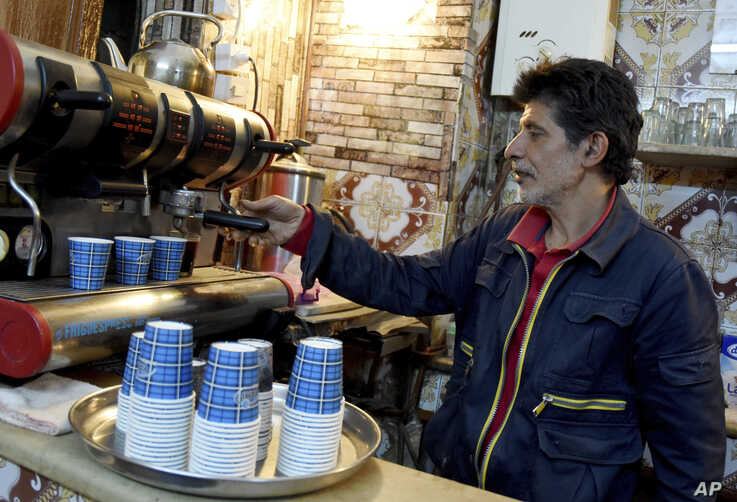 A man prepares some coffees for customers in a cafe of Tunis, Tuesday May 26, 2020.