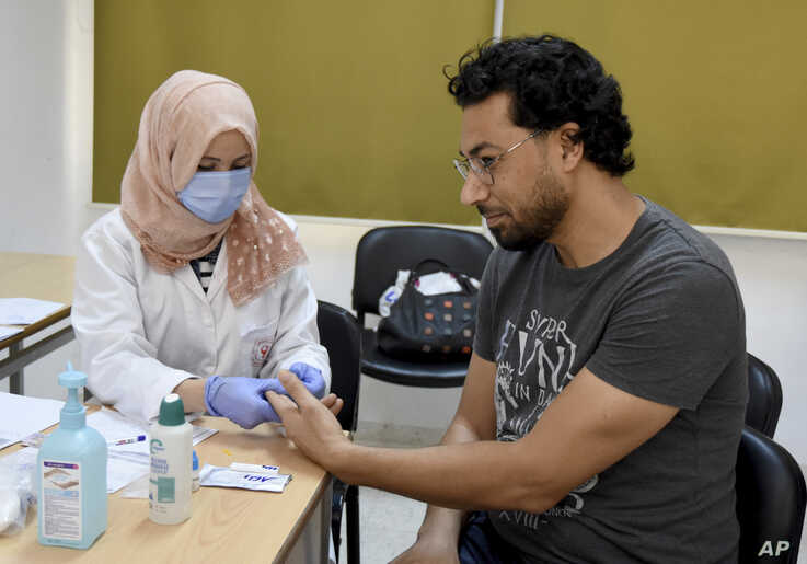 An employee of the Tunisian Health ministry takes a blood sample to test a teacher against the COVID-19 in a school of Tunis, Wednesday, May 27, 2020.
