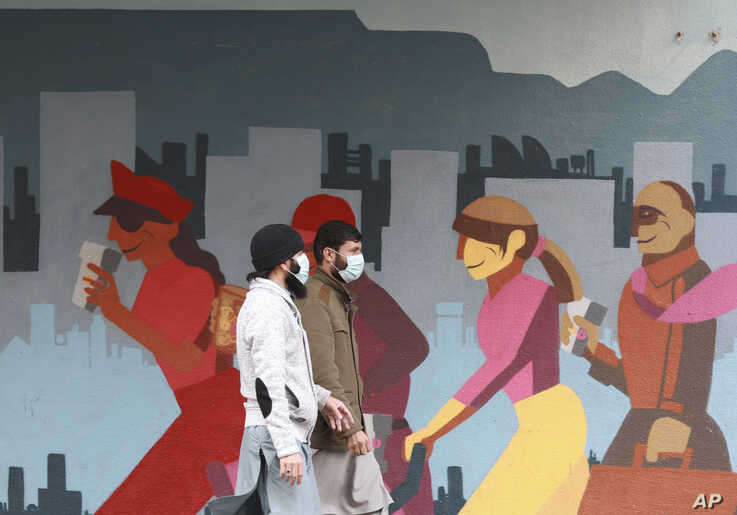 Men wearing face masks walk past a mural in Cape Town, South Africa, Wednesday, May 27, 2020. With dramatically increased…