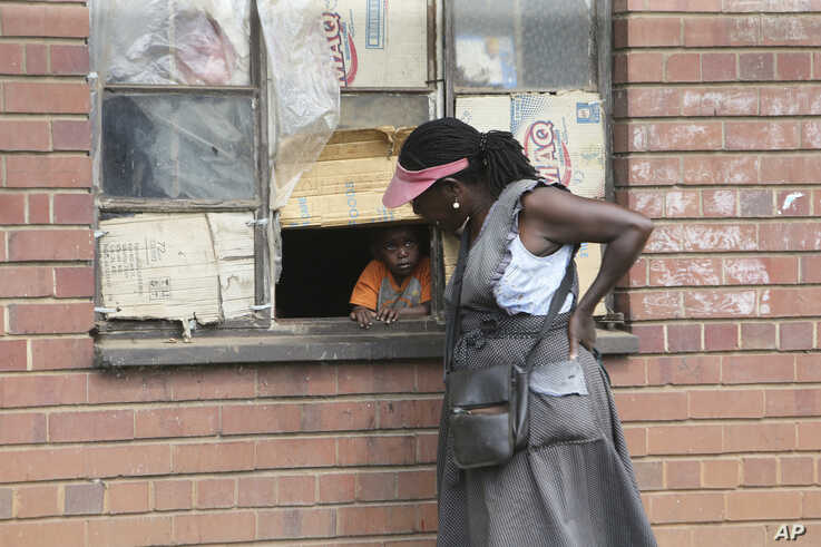 A woman talks to a child through a window in Harare, Thursday May 28, 2020. Manhunts have begun after hundreds of people, some…