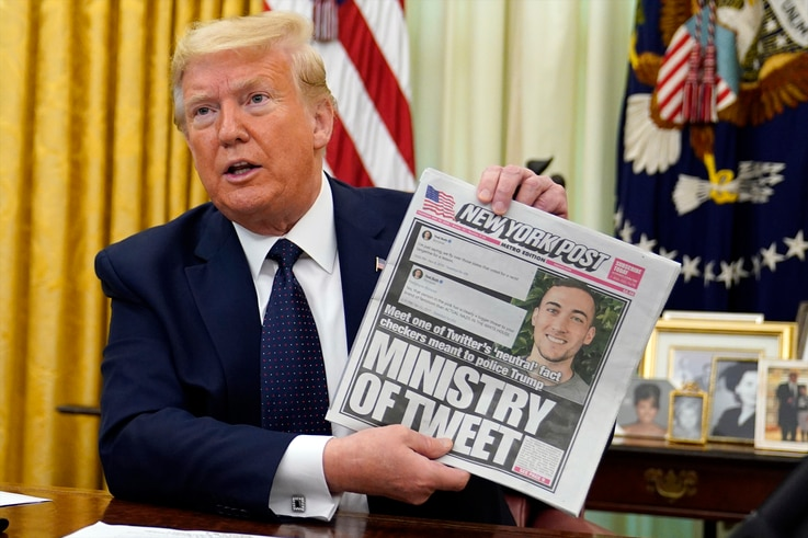 President Donald Trump holds up a copy of the New York Post as speaks before signing an executive order aimed at curbing…